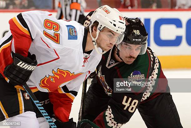 Jordan Martinook of the Arizona Coyotes and Michael Frolik of the Calgary Flames get ready during a faceoff at Gila River Arena on November 27 2015...