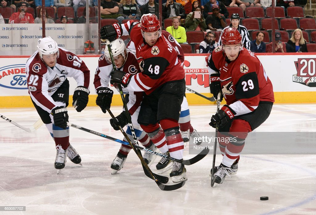 Jordan Martinook #48 of the Arizona Coyotes and Mikko Rantanen #96 of the Colorado Avalanche battle as Brendan Perlini #29 of the Coyotes skates in for the loose puck during the first period at Gila River Arena on March 13, 2017 in Glendale, Arizona.