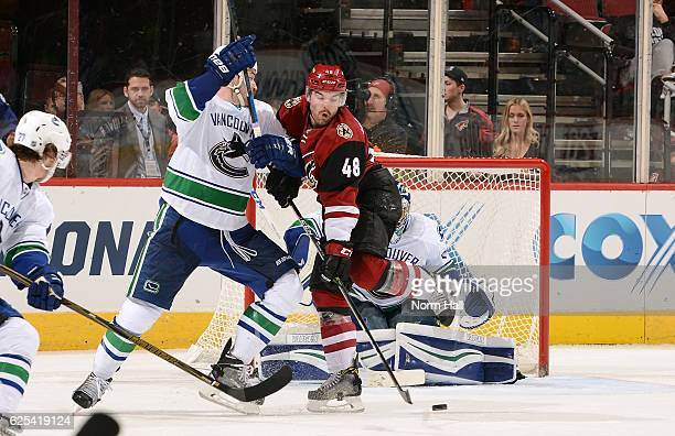 Jordan Martinook of the Arizona Coyotes battles with Erik Gudbranson of the Vancouver Canucks as he attempts to redirect the puck during the third...