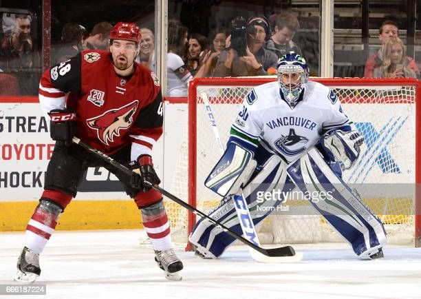 Jordan Martinook of the Arizona Coyotes looks for the puck as Ryan Miller of the Vancouver Canucks gets ready to make a save at Gila River Arena on...