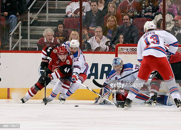 Jordan Martinook of the Arizona Coyotes skates with the puck in front of goaltender Antti Raanta of the New York Rangers as Dan Boyle and Kevin Hayes...
