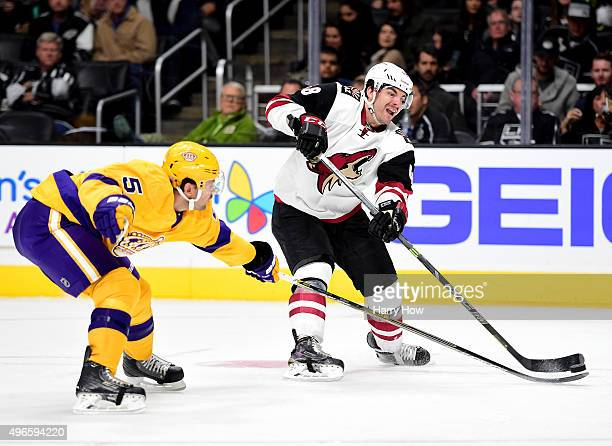Jordan Martinook of the Arizona Coyotes takes a shot as Jamie McBain of the Los Angeles Kings reaches to deflect during the third period at Staples...