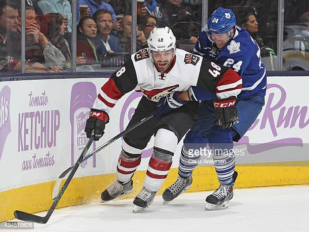 Jordan Martinook of the Arizona Coyotes tries to get away from a checking Peter Holland of the Toronto Maple Leafs during an NHL game at the Air...