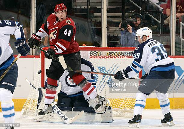 Jordan Martinookk of the Arizona Coyotes tries to redirect the puck in front of goalie Connor Hellebuyck and Toby Enstrom of the Winnipeg Jets during...