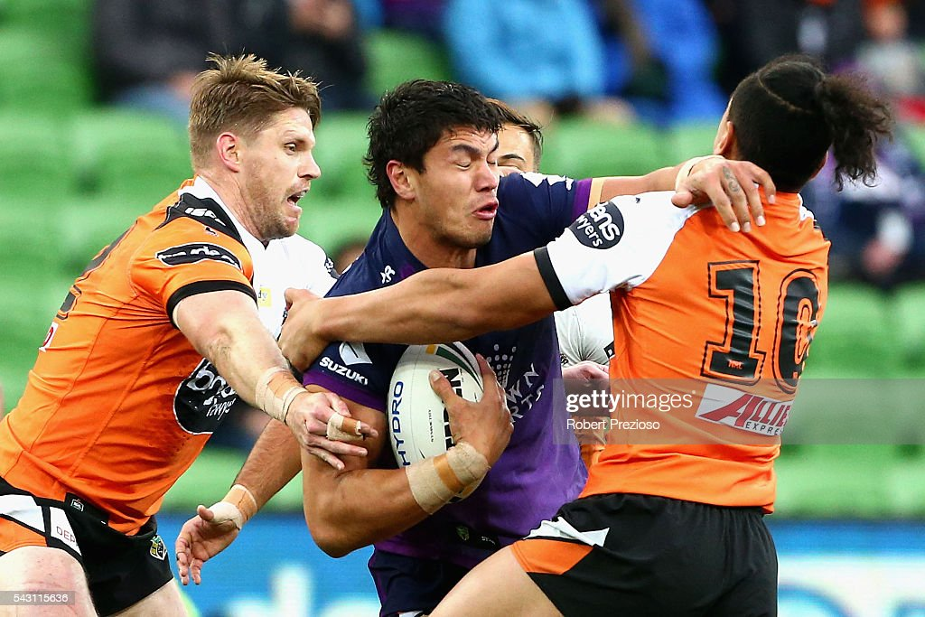Jordan McLean of the Storm is tackled during the round 16 NRL match between the Melbourne Storm and Wests Tigers at AAMI Park on June 26, 2016 in Melbourne, Australia.