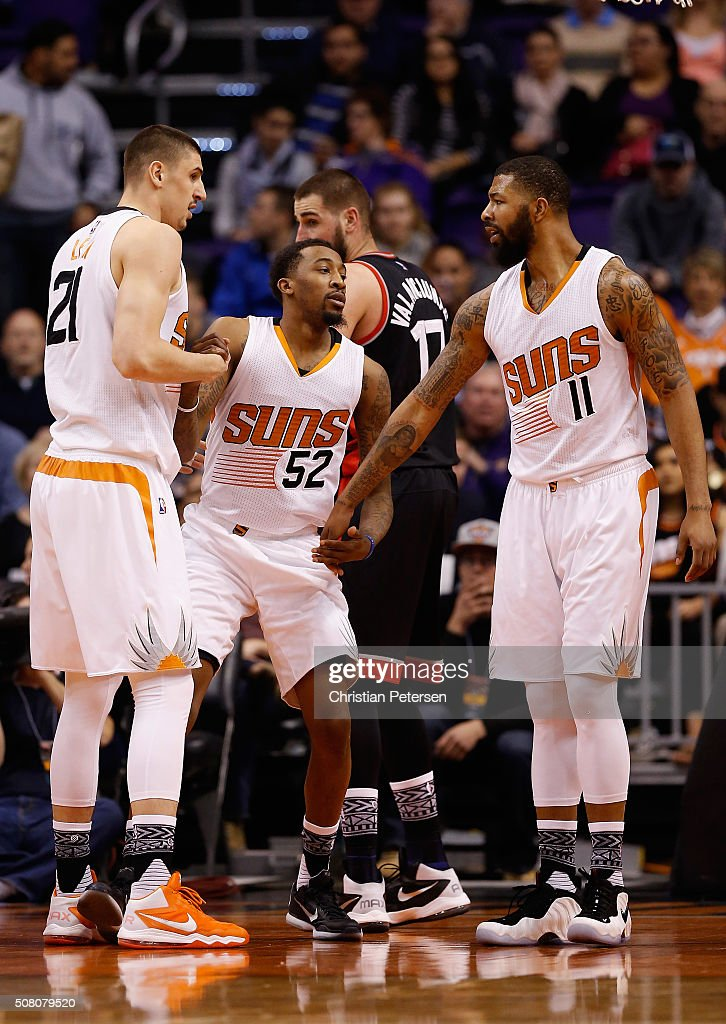 Jordan McRae of the Phoenix Suns is helped up by Alex Len and Markieff Morris after scoring against the Toronto Raptors during the first half of the...
