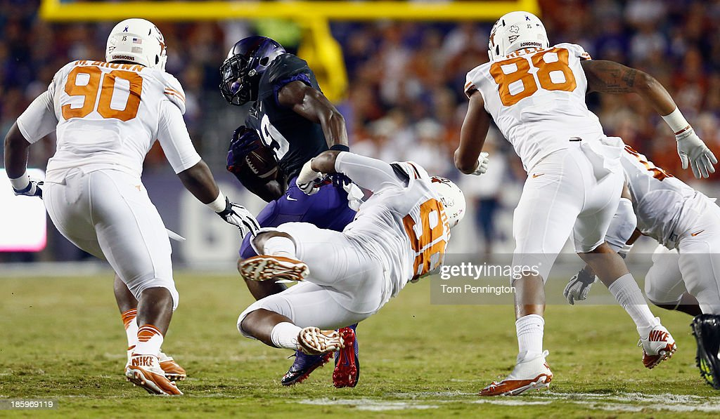 Jordan Moore #29 of the TCU Horned Frogs carries the ball against Chris Whaley #96 of the Texas Longhorns, Malcom Brown #90 of the Texas Longhorns, and Cedric Reed #88 of the Texas Longhorns in the first quarter at Amon G. Carter Stadium on October 26, 2013 in Fort Worth, Texas.