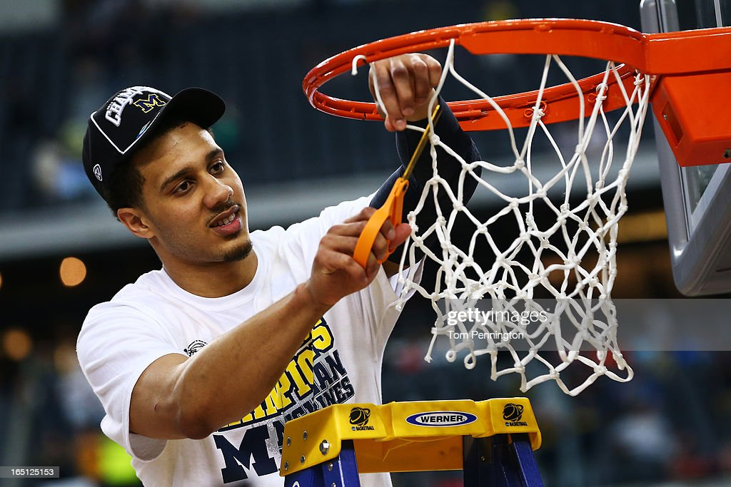 Jordan Morgan #52 of the Michigan Wolverines celebrates their 79 to 59 win over the Florida Gators by cutting down a piece of the net during the South Regional Round Final of the 2013 NCAA Men's Basketball Tournament at Dallas Cowboys Stadium on March 31, 2013 in Arlington, Texas.