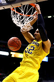 Jordan Morgan of the Michigan Wolverines dunks the ball in the second half against the Tennessee Volunteers during the regional semifinal of the 2014...