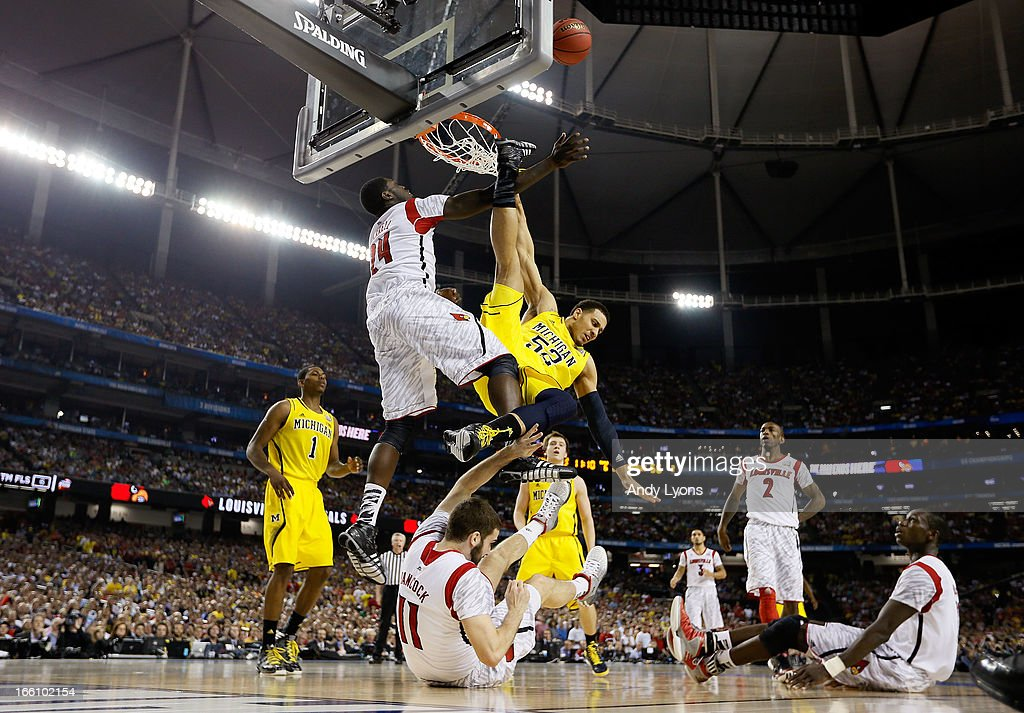 Jordan Morgan #52 of the Michigan Wolverines falls to the court after he attempted a shot against <a gi-track='captionPersonalityLinkClicked' href=/galleries/search?phrase=Montrezl+Harrell&family=editorial&specificpeople=9959702 ng-click='$event.stopPropagation()'>Montrezl Harrell</a> #24 and <a gi-track='captionPersonalityLinkClicked' href=/galleries/search?phrase=Luke+Hancock&family=editorial&specificpeople=6560051 ng-click='$event.stopPropagation()'>Luke Hancock</a> #11 of the Louisville Cardinals during the 2013 NCAA Men's Final Four Championship at the Georgia Dome on April 8, 2013 in Atlanta, Georgia.