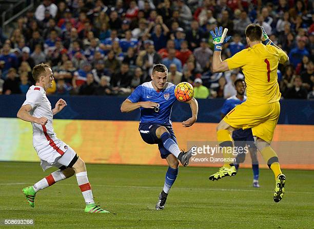 Jordan Morris of the United States lifts the ball above goalkeeper Maxime Crepeau of Canada as he attempts to score during the first half of their...