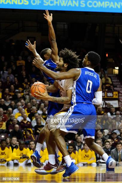 Jordan Murphy of the Minnesota Golden Gophers shoots the ball against De'Antae McMurray and CJ Rivers of the Drake Bulldogs during the game on...