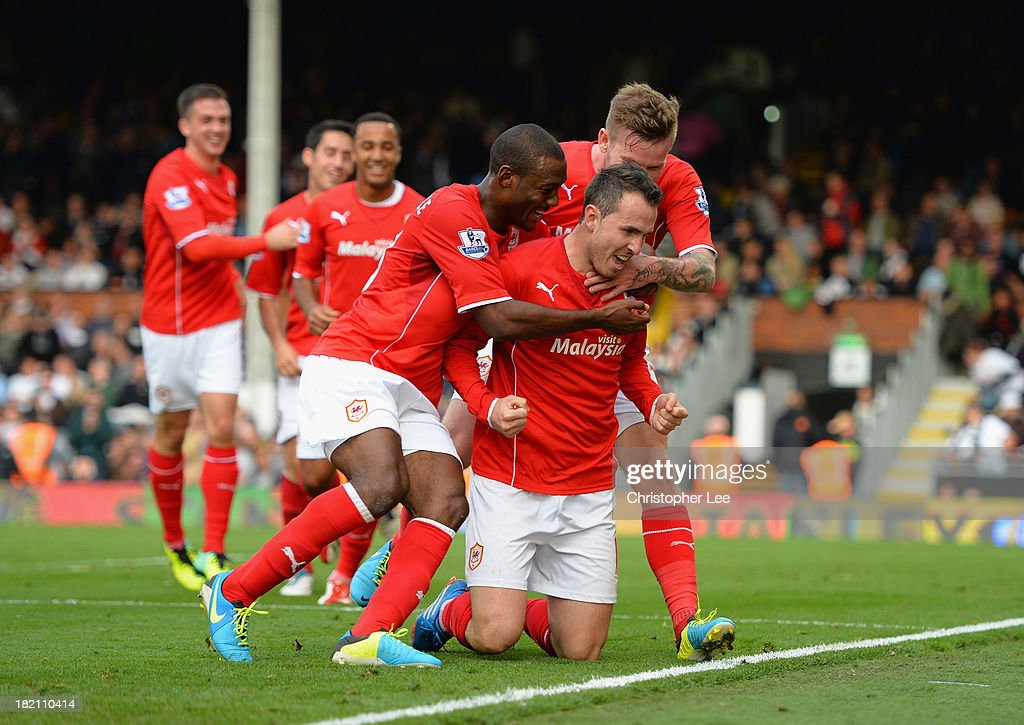 Jordan Mutch of Cardiff is mobbed by his team mates as he celebrates on his knees after scoring their winning goal during the Barclays Premier League match between Fulham and Cardiff City at Craven Cottage on September 28, 2013 in London, England.