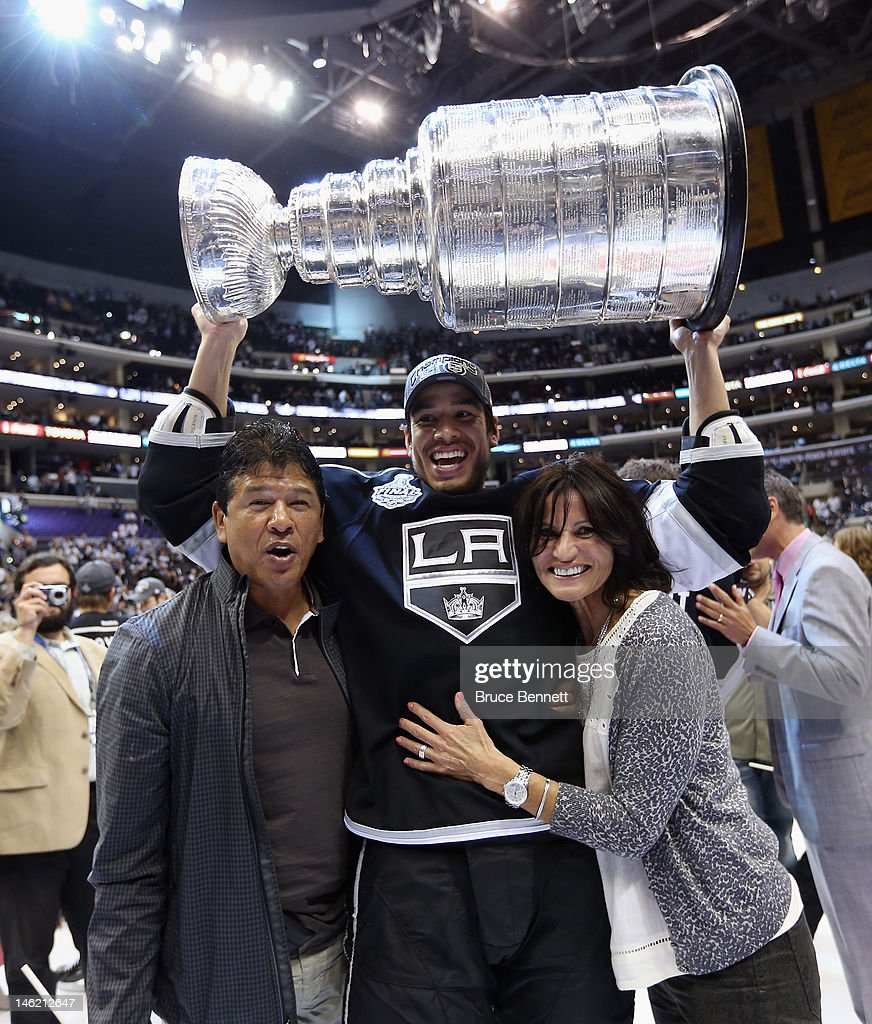 Jordan Nolan of the Los Angeles Kings holds up the Stanley Cup flanked by his parents former NHL coach Ted Nolan and his mother Sandra after the...