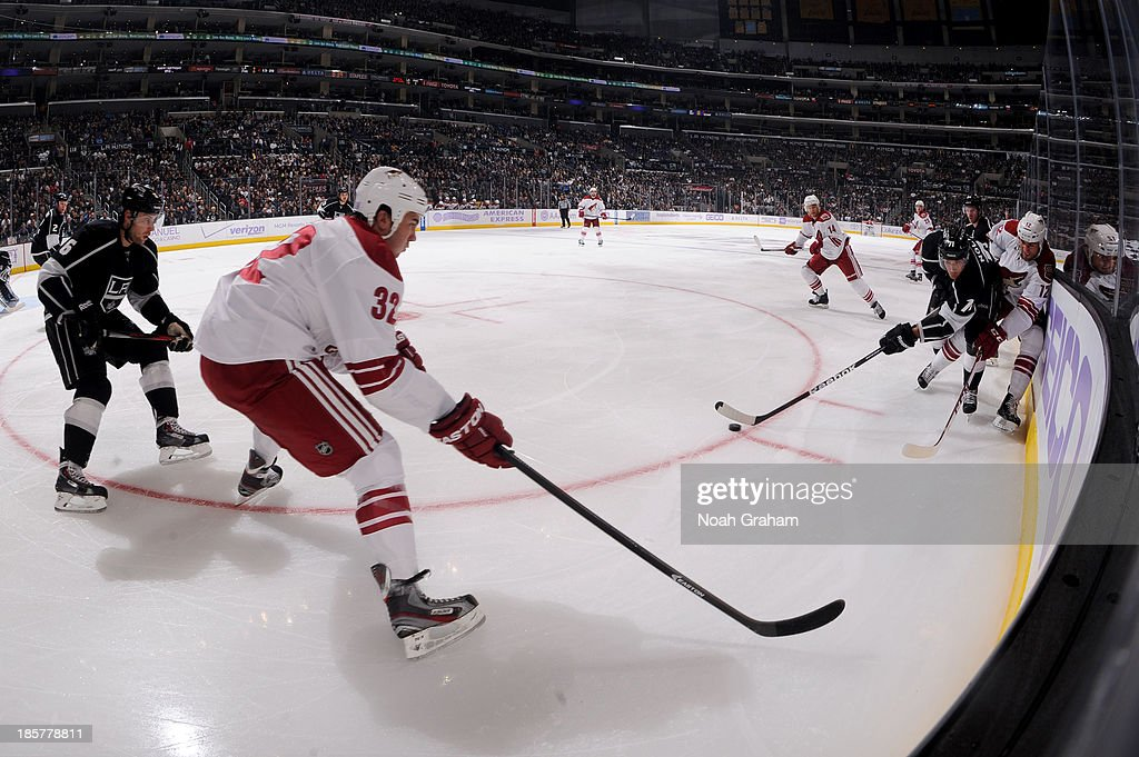 Jordan Nolan of the Los Angeles Kings skates with the puck against Paul Bissonnette and Brandon Yip of the Phoenix Coyotes at Staples Center on...