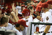 Jordan Pacheco of the Arizona Diamondbacks is congratulated by teammates in the dugout after scoring a first inning run against the Kansas City...