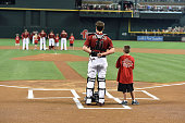 Jordan Pacheco of the Arizona Diamondbacks stands at home plate with a young fan during the singing of the national anthem prior to a game against...
