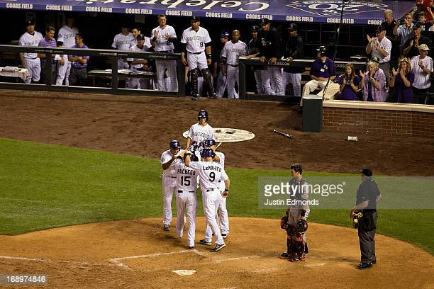 Jordan Pacheco of the Colorado Rockies is mobbed at home plate after hitting a goahead grand slam during the fifth inning giving the Rockies a 95...