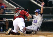 Jordan Pacheco of the Colorado Rockies is tagged out at home plate by catcher Miguel Montero of the Arizona Diamondbacks as he attempts to score a...