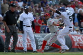 Jordan Pacheco of the Colorado Rockies is tagged out by Freddy Galvis of the Philadelphia Phillies after being caught in a run down as third base...