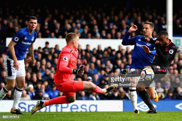 Jordan Pickford of Everton attempts to save a shot by Alexandre Lacazette of Arsenal during the Premier League match between Everton and Arsenal at...
