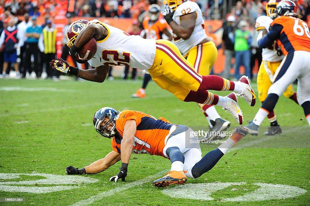 Jordan Pugh #32 of the Washington Redskins returns an interception against Eric Decker #87 of the Denver Broncos at Sports Authority Field on October 27, 2013 in Denver, Colorado.