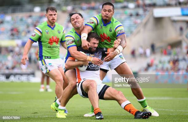 Jordan Rapana and Joseph Leilua of the Raiders tackle James Tedesco of the Tigers during the round three NRL match between the Canberra Raiders and...