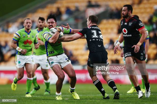Jordan Rapana of the Raiders fends against Ryan Hoffman of the Warriors during the round 23 NRL match between the New Zealand Warriors and the...