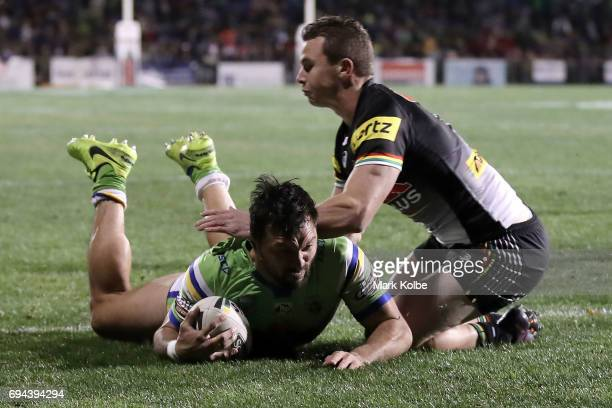 Jordan Rapana of the Raiders scores atry under pressure from Dylan Edwards of the Panthers during the round 14 NRL match between the Penrith Panthers...