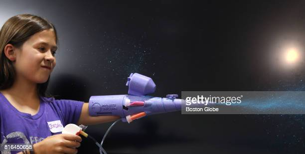 Jordan Reeves demonstrates her 'Glitter Blaster' during the Superhero Cyborgs oneday design event held for children with missing limbs at Canopy City...