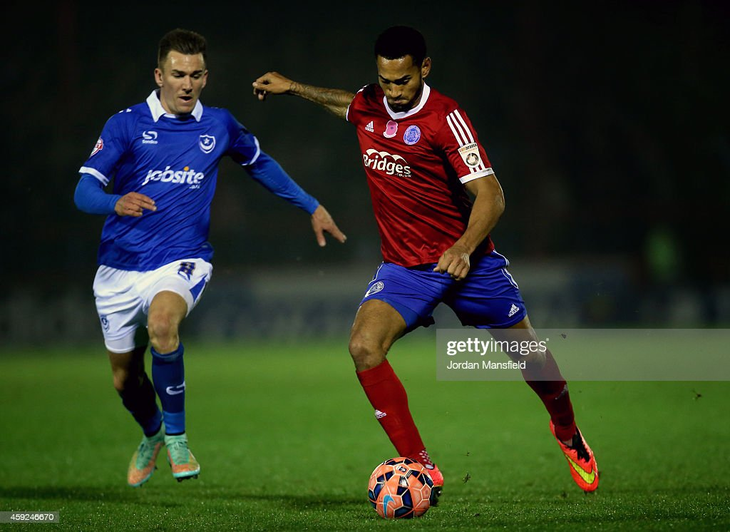 Jordan Roberts of Aldershot takes a shot on goal under pressure from Jed Wallace of Portsmouth during the FA Cup First Round Replay match between...