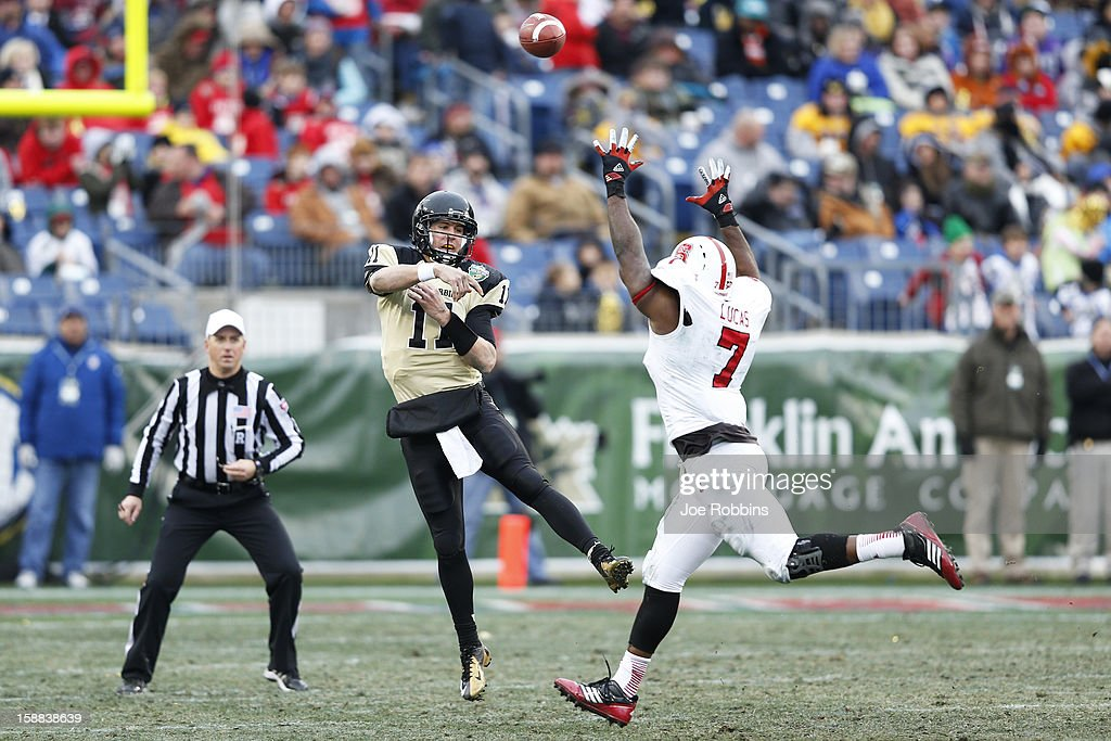 Jordan Rodgers #11 of the Vanderbilt Commodores passes the ball while under pressure from Sterling Lucas #7 of the North Carolina State Wolfpack during the Franklin American Mortgage Music City Bowl at LP Field on December 31, 2012 in Nashville, Tennessee. Vanderbilt won 38-24.