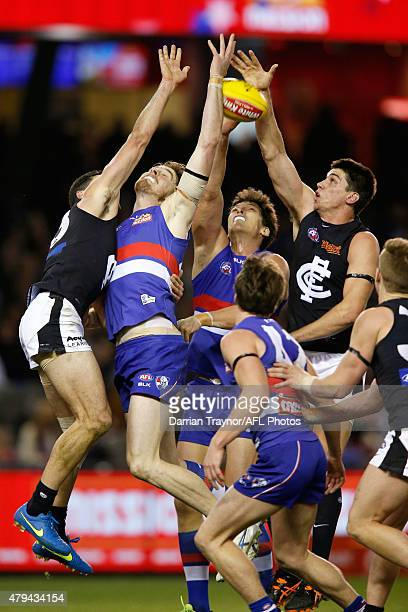 Jordan Roughead and Will Minson of the Bulldogs compete with Matthew Kreuzer of the Blues during the round 14 AFL match between the Western Bulldogs...