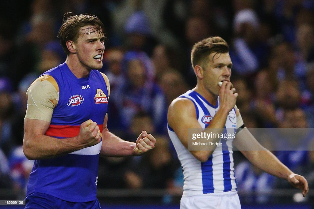 Jordan Roughead of the Bulldogs celebrates a goal next to Shaun Higgins of the Kangaroos during the round 22 AFL match between the North Melbourne Kangaroos and the Western Bulldogs at Etihad Stadium on August 29, 2015 in Melbourne, Australia.