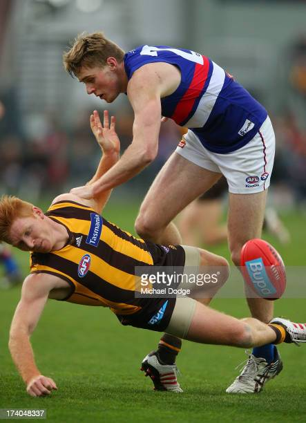 Jordan Roughead of the Bulldogs knocks down Kyle Cheney of the Hawks after he marked the ball during the round 17 AFL match between the Hawthorn...