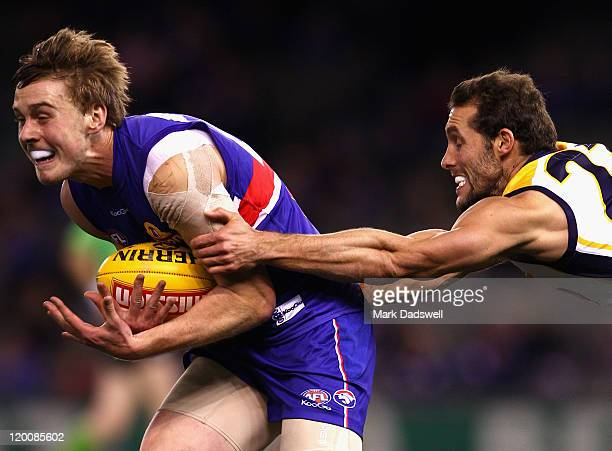 Jordan Roughead of the Bulldogs marks under pressure from Darren Glass of the Eagles during the round 19 AFL match between the Western Bulldogs and...