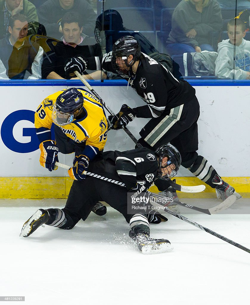 Jordan Samuels-Thomas #19 of the Quinnipiac University Bobcats is checked by Conor MacPhee #29 and Tom Parisi #6 of the Providence College Friars during the NCAA Division I Men's Ice Hockey East Regional Championship Semifinal at Webster Bank Arena on March 28, 2014 in Bridgeport, Connecticut.