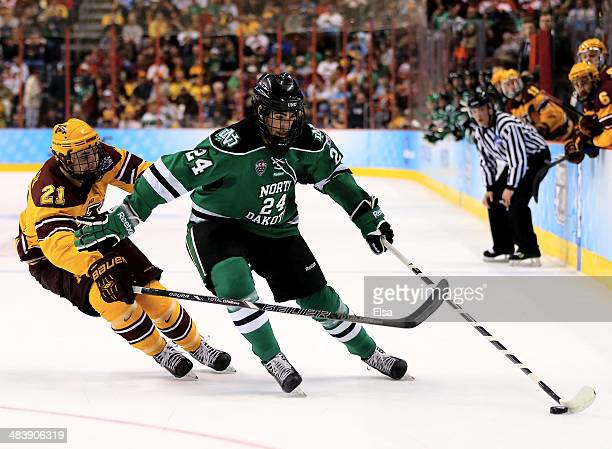 Jordan Schmaltz of the North Dakota Fighting Sioux takes the puck as Conner Reilly of the Minnesota Gophers defends in the first period during the...