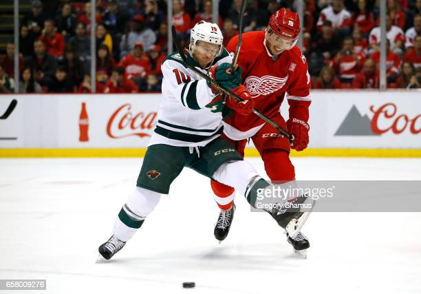 Jordan Schroeder of the Minnesota Wild battles for the puck with Robbie Russo of the Detroit Red Wings during the first period at Joe Louis Arena on...