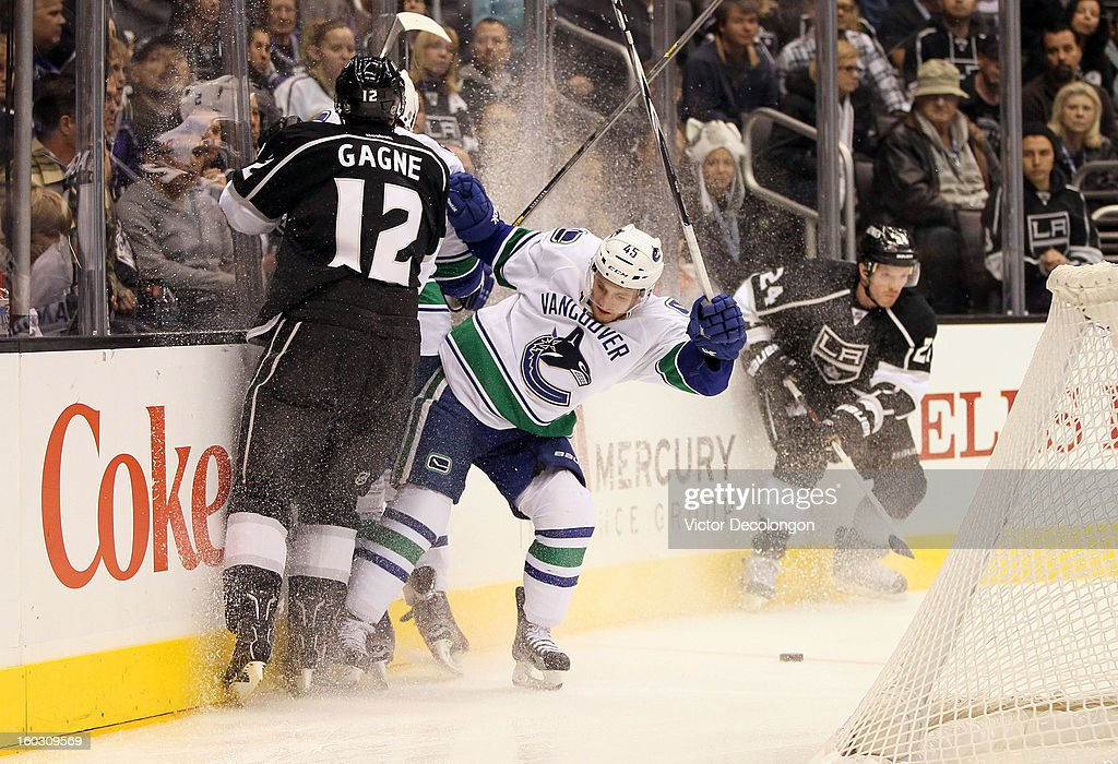 <a gi-track='captionPersonalityLinkClicked' href=/galleries/search?phrase=Jordan+Schroeder&family=editorial&specificpeople=4450940 ng-click='$event.stopPropagation()'>Jordan Schroeder</a> #45 of the the Vancouver Canucks and Simon Gagne #12 of the Los Angeles Kings vie for the puck behind the net in the second period during the NHL game at Staples Center on January 28, 2013 in Los Angeles, California. The Kings defeated the Canucks 3-2 in shootout overtime.