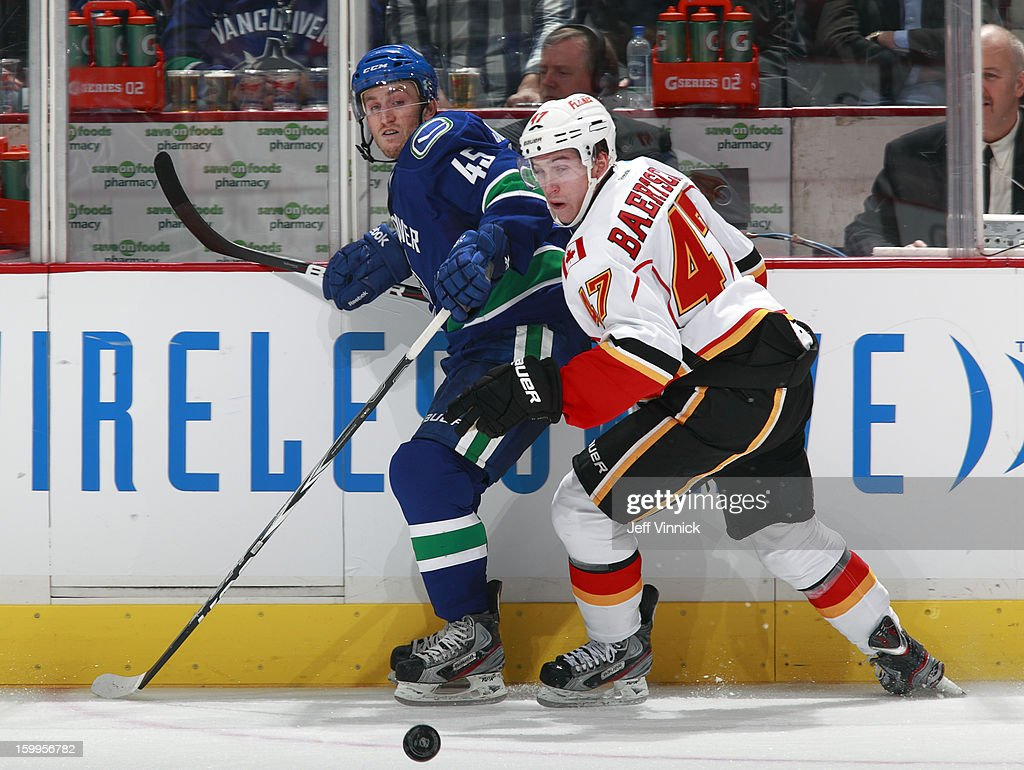 <a gi-track='captionPersonalityLinkClicked' href=/galleries/search?phrase=Jordan+Schroeder&family=editorial&specificpeople=4450940 ng-click='$event.stopPropagation()'>Jordan Schroeder</a> #45 of the Vancouver Canucks and <a gi-track='captionPersonalityLinkClicked' href=/galleries/search?phrase=Sven+Baertschi&family=editorial&specificpeople=7832299 ng-click='$event.stopPropagation()'>Sven Baertschi</a> #47 of the Calgary Flames watch a loose puck during their NHL game at Rogers Arena January 23, 2013 in Vancouver, British Columbia, Canada. Vancouver won 3-2 in a shootout.