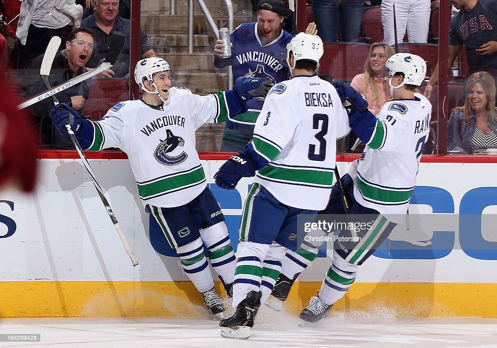 <a gi-track='captionPersonalityLinkClicked' href=/galleries/search?phrase=Jordan+Schroeder&family=editorial&specificpeople=4450940 ng-click='$event.stopPropagation()'>Jordan Schroeder</a> #45 of the Vancouver Canucks celebrates with <a gi-track='captionPersonalityLinkClicked' href=/galleries/search?phrase=Kevin+Bieksa&family=editorial&specificpeople=688792 ng-click='$event.stopPropagation()'>Kevin Bieksa</a> #3 and <a gi-track='captionPersonalityLinkClicked' href=/galleries/search?phrase=Mason+Raymond&family=editorial&specificpeople=4521385 ng-click='$event.stopPropagation()'>Mason Raymond</a> #21 after Schroeder scored a third period goal against the Phoenix Coyotes during the NHL game at Jobing.com Arena on March 21, 2013 in Glendale, Arizona. The Canucks defeated the Coyotes 2-1.