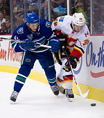 Jordan Schroeder of the Vancouver Canucks delivers a check to Ben Street of the Calgary Flames during the third period in NHL action on February 09...