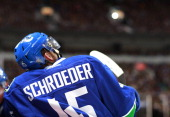 Jordan Schroeder of the Vancouver Canucks looks on from the bench during their NHL game against the Dallas Stars at Rogers Arena February 15 2013 in...