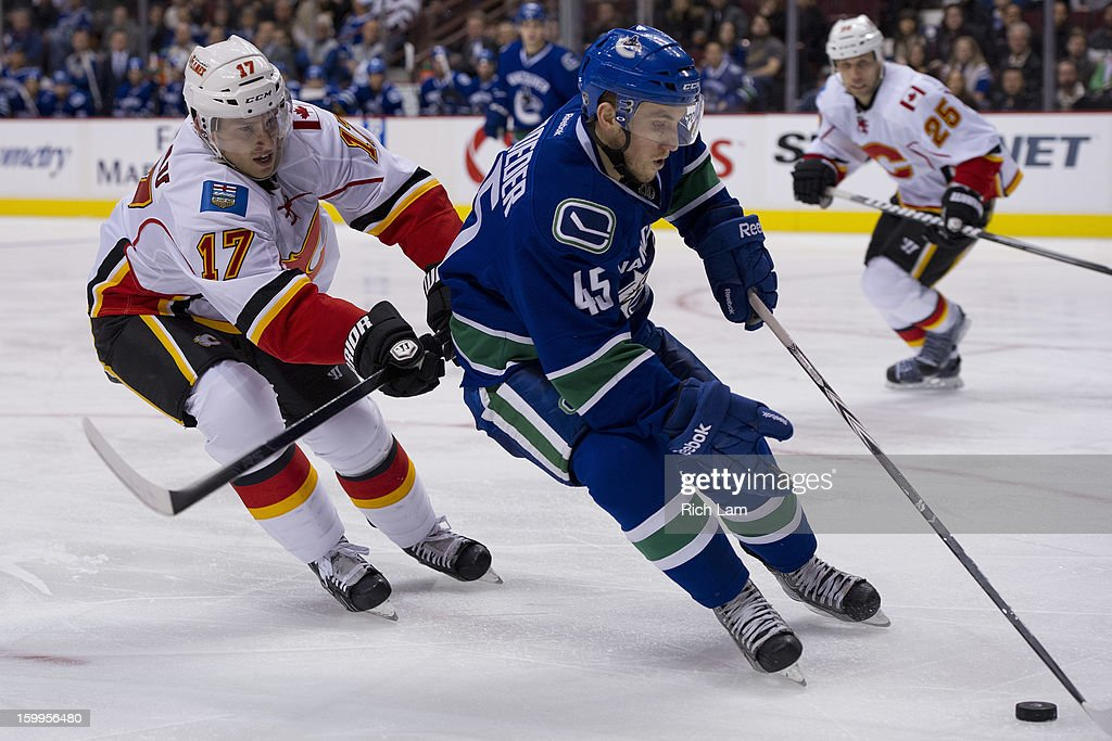 <a gi-track='captionPersonalityLinkClicked' href=/galleries/search?phrase=Jordan+Schroeder&family=editorial&specificpeople=4450940 ng-click='$event.stopPropagation()'>Jordan Schroeder</a> #45 of the Vancouver Canucks tries to break free from the check of <a gi-track='captionPersonalityLinkClicked' href=/galleries/search?phrase=Blake+Comeau&family=editorial&specificpeople=879782 ng-click='$event.stopPropagation()'>Blake Comeau</a> #17 of the Calgary Flames during the third period of NHL action on January 23, 2013 at Rogers Arena in Vancouver, British Columbia, Canada. Schroeder was playing in his first NHL game.