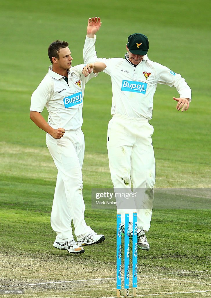 Jordan Silk and Evan Gulbis of Tasmania celebrate the wicket of Peter Handscomb of Victoria during day two of the Sheffield Shield match between the Tasmania Tigers and the Victoria Bushrangers at Blundstone Arena on March 15, 2013 in Hobart, Australia.