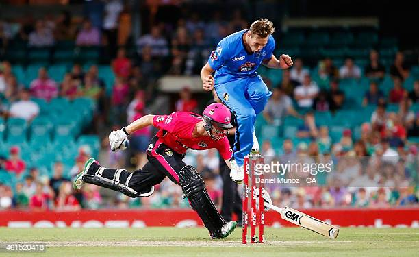 Jordan Silk of the Sixers makes his ground as Ben Laughlin of the Strikers jumps during the Big Bash League match between the Sydney Sixers and the...