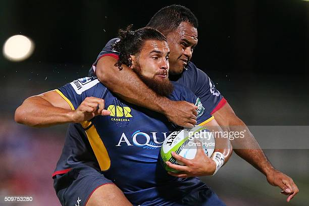 Jordan Smiler of the Brumbies is tackled by Sam Talakai of the Reds during the Super Rugby PreSeason match between the Reds and the Brumbies at...