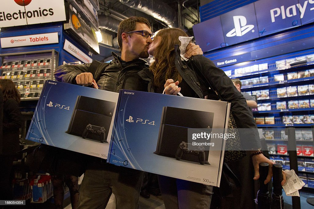 Jordan Smith, left, and Kayla Brittingham, share a kiss after purchasing the Sony PlayStation 4 console during its midnight launch event in San Francisco, California, U.S., on Thursday, Nov. 14, 2013. Sony Corp., poised to release the PlayStation 4 game console this week, is confident it can meet analysts' sales estimates of 3 million units by year-end, exploiting an early advantage over Microsoft Corp.'s Xbox One. Photographer: Erin Lubin/Bloomberg via Getty Images