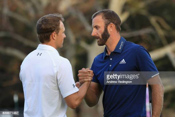Jordan Spieth and Dustin Johnson of the United States shake hands after Johnson putted for birdie on the 18th green to defeat Spieth in a playoff to...